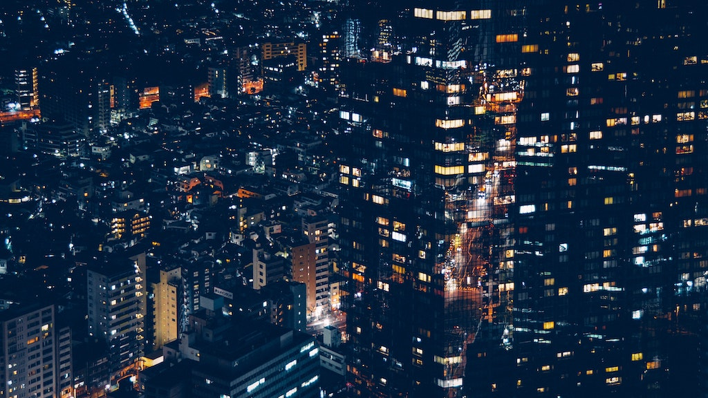 City and buildings at night with lights on, powered by the electricity grid.